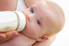 Bond little baby blue eyes drinking bottle milk. Bond little baby with blue eyes drinking bottle milk in mother arms Royalty Free Stock Image