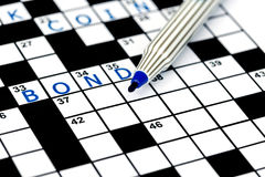Bond in solving crossword puzzle Stock Photo