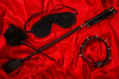 Bondage, kinky adult sex games, kink and BDSM lifestyle concept. With awhip, feather stick, collar, eye mask on red silk with copy space stock photo