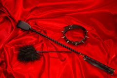 Bondage, kinky adult sex games, kink and BDSM lifestyle concept. With a whip, feather stick, collar on red silk with copy space stock photography