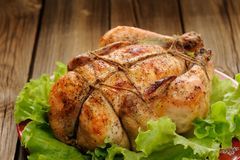 Bondage shibari roasted chicken with salad leaves on red plate o Stock Photo