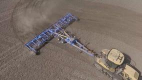 Bonde i traktoren som förbereder jordbruksmark med såbädden för det nästa året lager videofilmer