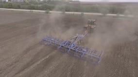 Bonde i traktoren som förbereder jordbruksmark med såbädden för det nästa året arkivfilmer
