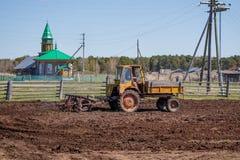 Bonde i traktoren som f?rbereder land med s?b?ddodlaren royaltyfri bild