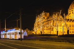 Bonde leve festiva decorado, Fenyvillamos, no movimento com o parlamento de Hungria no quadrado de Kossuth na noite Estação do Na imagens de stock