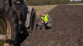 Bonde med dokumentation nära traktoren på fält stock video