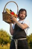 Bonde med en ekologisk skörd av grönsaker i en korg nära Royaltyfri Foto
