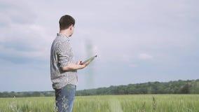 Bonde med rutigt skjortaanseende för svart hår och а i fältet av grönt vete och arbete med en minnestavla i fältet lager videofilmer