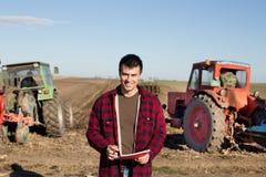Bonde med traktorer på fält Royaltyfri Fotografi