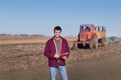 Bonde med traktorer på fält Arkivbilder