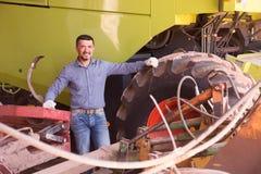 Bonde nära agrimotor med stora hjul Fotografering för Bildbyråer