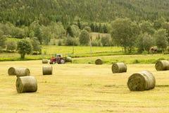 Bonde på traktoren med höbaler Royaltyfri Bild