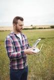 Bonde som använder den jordbruks- apparaten, medan undersöka i fält royaltyfria foton