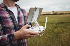 Bonde som använder den jordbruks- apparaten, medan undersöka i fält Arkivbild