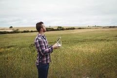 Bonde som använder den jordbruks- apparaten, medan undersöka i fält Fotografering för Bildbyråer