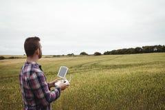 Bonde som använder den jordbruks- apparaten, medan undersöka i fält royaltyfri foto