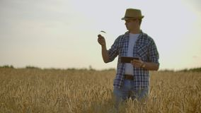 Bonde som anv?nder minnestavlan i vetef?lt Forskare som arbetar i f?lt med ?kerbruk teknologi Slut upp av manhanden arkivfilmer