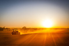 Bonde som förbereder hans fält i en traktor som är klar för vår