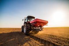 Bonde som gödslar åkermark med gasformigt grundämne, fosfor, kaliumgödningsmedel royaltyfri fotografi