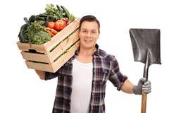 Bonde som rymmer en spjällåda med grönsaker arkivbild