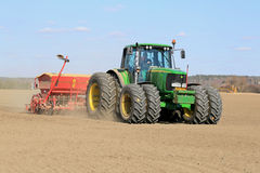 Bonde Working fältet med John Deere Tractor och seederen Fotografering för Bildbyråer