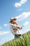 Bondeanseende i ett vetefält och samtal på telefonen arkivbild