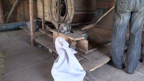 Bondearbete med den manuella kornrengöringsmedelharpan i byladugård stock video