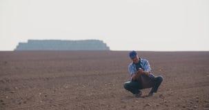 BondeExamining Soil In jordbruks- fält, jordbruk, lantbruk, ekologi lager videofilmer