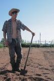 Bondegrabb med skyffeln på fri jord arkivbild