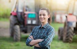 Bondekvinna med traktorer på jordbruksmark royaltyfria bilder