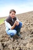 Bondekvinna som verifierar jorden i fälten royaltyfri foto