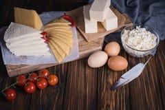 Bondelivsmedelsprodukter: mjölka, laga mat med grädde, ost, ägg, stugan, smör Lantlig sammansättning Collage av nya grönsaker arkivbild