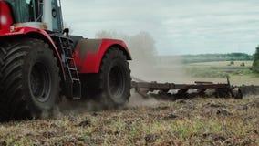 Bonden i traktor förbereder land med såbäddodlaren i tidig vårsäsong av jordbruks- arbeten på jordbruksmarker lager videofilmer