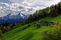Bondgård i sceniskt landskap på Watzmann bergskedja Royaltyfri Fotografi