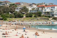 Bondi Beach Apartments and Beach Day. SYDNEY,NSW,AUSTRALIA-NOVEMBER 21,2016: Bondi Beach crowds with the Pacific Ocean waters, mosaic sea wall and housing Stock Photography