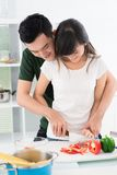 Bonding. Couple bonding while cooking together in the kitchen stock photography