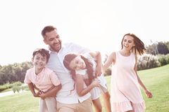 Bonding. Family of four walking on grassy field father carrying. Kids laughing playful royalty free stock image