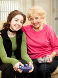 Bonding Over Video Games. Grandmother and teen granddaughter bonding by playing video games together Royalty Free Stock Photos