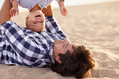 Bonding time with dad. Little boy toddler laughing as his dad is playing by turning him upside down Royalty Free Stock Images