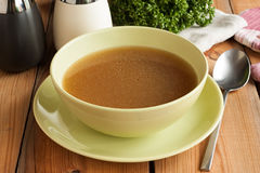 Bone broth made from beef, served in a soup bowl Royalty Free Stock Photos