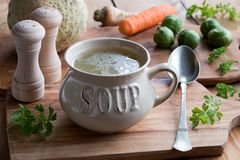 Bone broth made from chicken in a soup bowl. With vegetables in the background Stock Images
