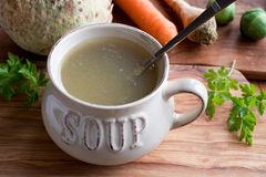 Bone broth made from chicken in a soup bowl on a wooden table. With vegetables in the background Royalty Free Stock Image