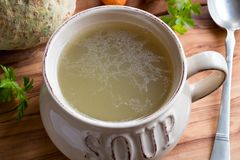Bone broth made from chicken in a soup bowl on a wooden table. Bone broth made from chicken in a soup bowl, with celery root and parsley in the background Stock Images