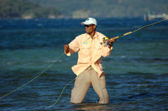 Bone Fishing in Honduras. Fishing guide in Honduras shows concentration while casting a heavy fly, which can be seen moving from left to right, in front of his Stock Photo