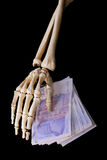 Bone hand with money Royalty Free Stock Photo