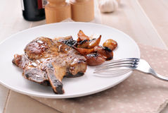 Bone-in pork chop with caramelized onions Stock Image