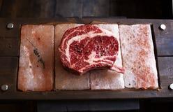 Bone In Rib Eye row Steak on pieces of salt Royalty Free Stock Photo