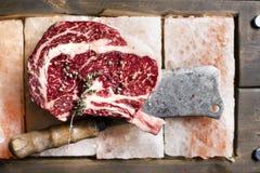 Bone In Rib Eye row Steak on pieces of salt Royalty Free Stock Photos