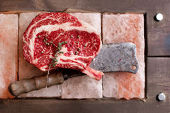 Bone In Rib Eye row Steak on pieces of salt Royalty Free Stock Images