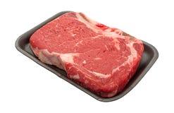 Bone in rib eye steak on black butcher tray Royalty Free Stock Photography